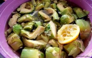 Alcachofas cortadas y metidas en un recipiente con agua y el zumo de 1/2 limón